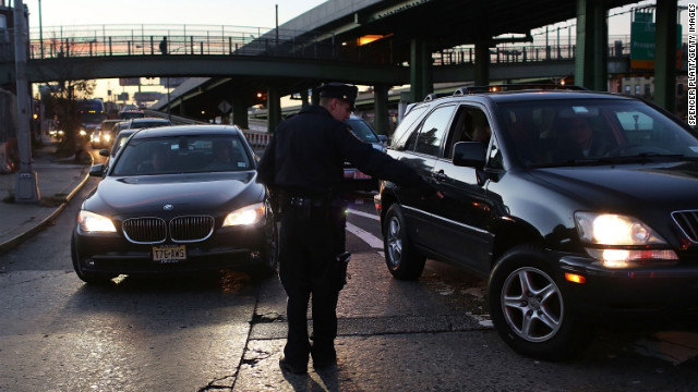 A police officer checks cars entering the Brooklyn Queens Expressway to confirm that they have three occupants before allowing them to cross into Manhattan on Thursday. Limited public transit has returned to New York, and most major bridges have reopened. However, vehicles must have three occupants to pass.