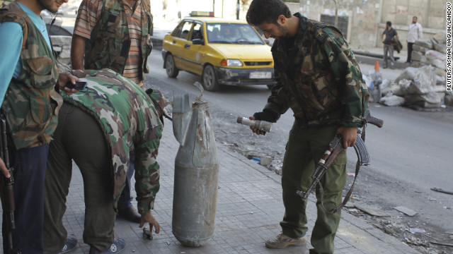 Members of the Free Syrian Army stand close to an unexploded bomb dropped by a fighter jet weeks earlier, at a checkpoint in Aleppo on Thursday, November 1.