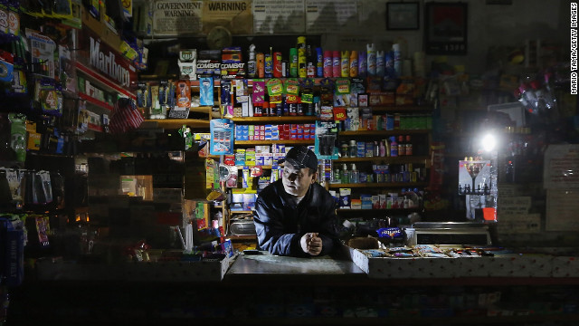 Park Choul works by flashlight in his deli in New York's East Village on Thursday, November 1. More than 3.3 million customers remained without electricity in 15 states and the District of Columbia four days after Sandy barreled ashore.