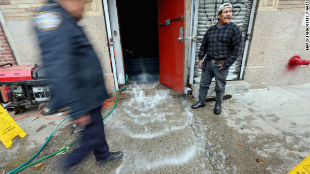 Water gets pumped out of a business in the East Village on Thursday.