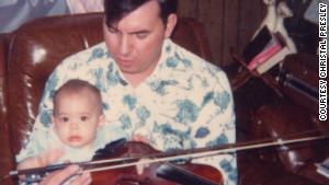 A baby Christal sits on Delmer\'s lap. He found solace in his music and would sometimes play the guitar eight hours a day.