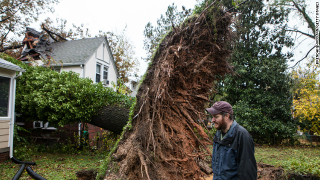 Sam Rigby walks by a tree that fell and grazed his house and hit his neighbor's house during Superstorm Sandy. 