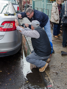 Residents try to siphon gasoline out of their flooded car to use in a generator on Thursday in Hoboken. Power had still not been restored to most of the city three days after Sandy's storm surge flooded the area.