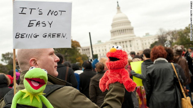 A man carrying puppets of Sesame Street characters Elmo and Kermit takes part in the