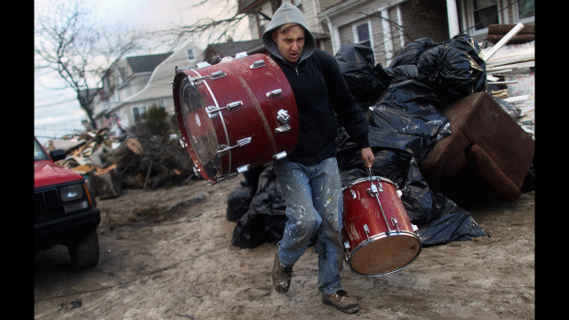 A man salvages a set of drums at Rockaway Beach in Queens, New York, on Saturday. Most of the Rockaway Peninsula remains without power.
