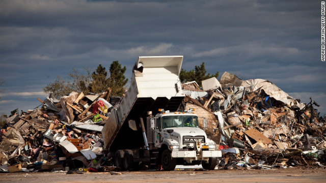 A dump truck empties trash collected from homes damaged by Superstorm Sandy on Saturday, November 3, in the Midland Beach neighborhood of Staten Island, New York. New York is trying to clean up and resume normal activities days after the storm hit.