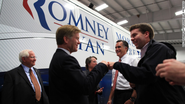 Romney smiles backstage with Virginia Gov. Bob McDonnell, left, who gives a fist bump to Romney aide Garrett Jackson after a rally in Richmond, Virginia, on Nov. 1, 2012.