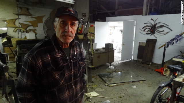 Artist and studio owner Silas Seandel works to restore his facility after floodwaters broke through his doors.