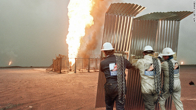 Specialist firefighters approach a burning well in a Kuwaiti oil field as they prepare an attempt to cap it in March 1991.