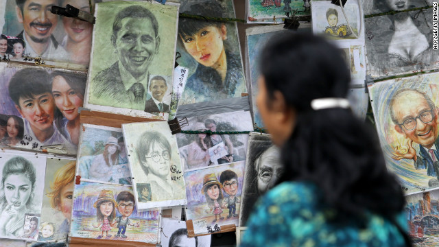A woman looks at caricatures of US President Barack Obama at a stall in Hong Kong. 