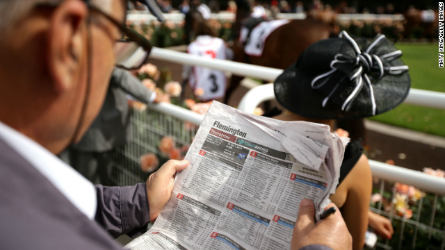 A racegoer watches the horses in the parade ring on Melbourne Cup Day on November 6, 2012. There's a public holiday in the state of Victoria each year on race day. Huge crowds go to the track while others hold parties at home and in restaurants, bars and clubs.