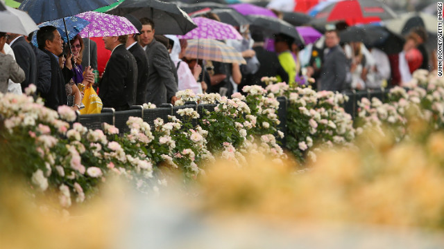 Crowds watch on from under umbrellas as rain starts to fall during 2012 Melbourne Cup Day. The day is a mix of formal attire featuring creative hats and comical outfits. 