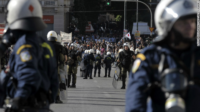 Riot police stand guard as demonstrators march in front of the Greek parliament in central Athens during the protests on November 6, 2012.