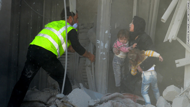 Syrian rescue workers evacuate a woman and her two children from a building targeted by an airstrike from government forces in a town northeast of Aleppo on Sunday, November 4. An AFP correspondent reported three air strikes on the town in close succession.