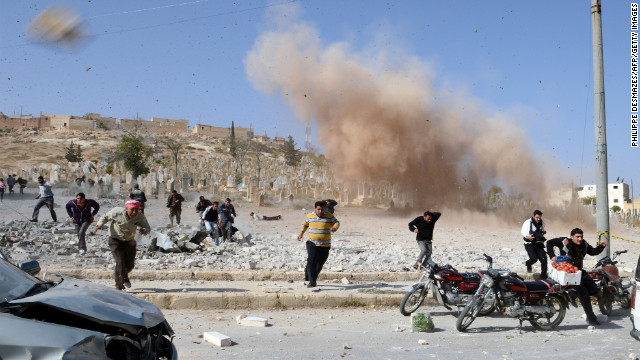 Syrian people take cover as a second bomb explodes during a rescue attempt in nearby a building that was hit during an air raid by government forces earlier on Sunday.