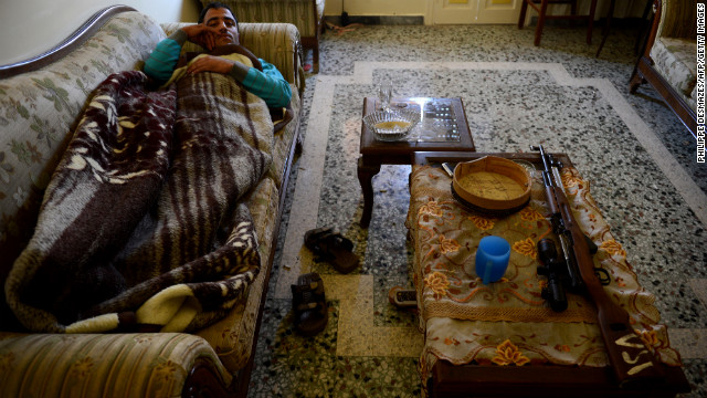 A Syrian rebel fighter rests on a couch in a rebel-controlled building on the front line in Aleppo's northern Izaa quarter on Sunday.