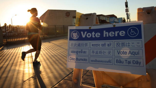 A jogger on The Strand in the Los Angeles area community of Hermosa Beach passes a directional sign to a polling place at sunrise Tuesday.