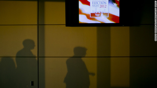Shadows were cast on a wall next to a television advertising &quot;Election Night 2012&quot; inside the Boston Convention &amp; Exhibition Center, where Republican presidential candidate Mitt Romney was scheduled to speak Tuesday evening.