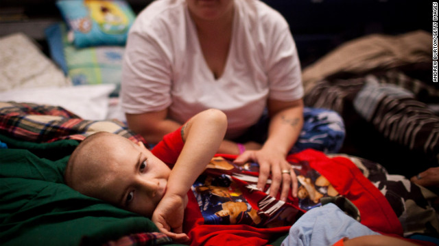 Michael Fischkelta, 8, lies on his cot with his mother, Jenifer Wilson, in a Red Cross evacuation shelter set up in the gymnasium of Toms River High School on Monday, November 5, in Toms River, New Jersey. View photos of the recovery efforts in New York.