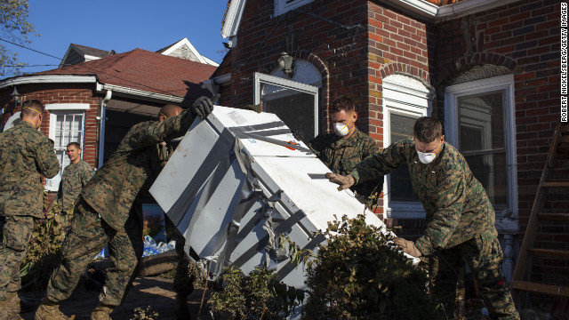 Troops from the 26th Marine Expeditionary Unit and the U.S. Navy help local residents remove household items damaged by Superstorm Sandy on November 6, in the New Dorp Beach neighborhood of Staten Island, New York.