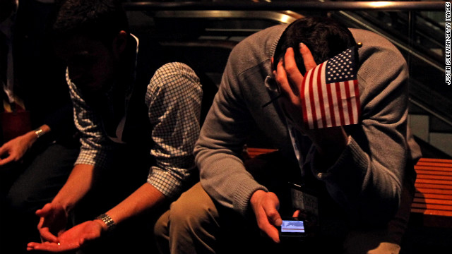 A supporter checks his smart phone while he waits for Republican Mitt Romney to give his concession speech in Boston, Massachusetts.
