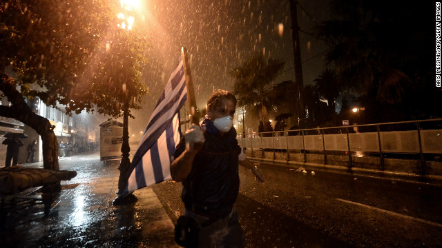 A man runs away from clashes between protesters and riot police outside the parliament in Athens on November 7, 2012.
