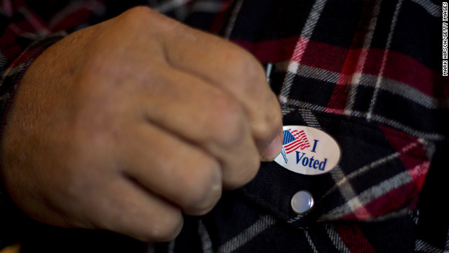  A man puts on an &quot;I Voted&quot; sticker after casting his ballot in Otter Creek, Iowa, on Tuesday. 
