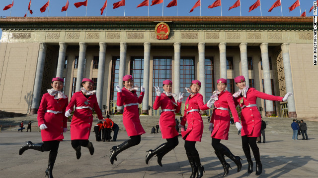 Chinese hostesses jump for the cameras before the Party Congress' opening session in Beijing.