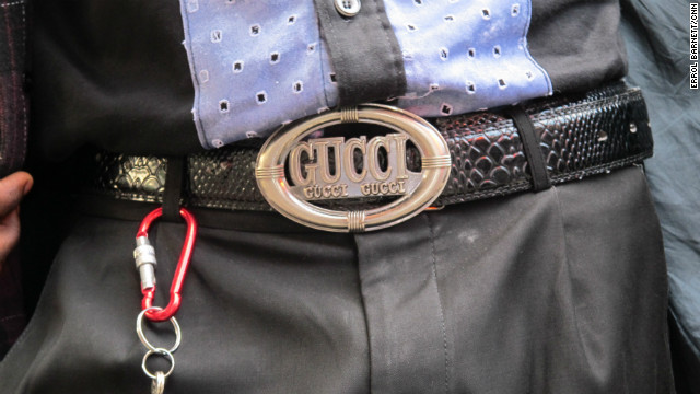 Name brands like Gucci are displayed boldly on belts, suit labels and sunglasses.