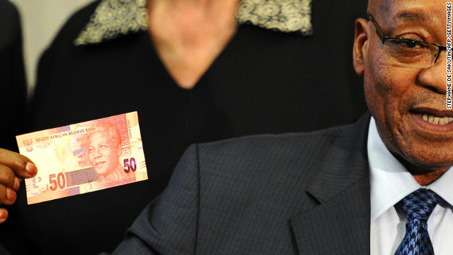 South African President Jacob Zuma shows a note featuring the country's former president Nelson Mandela.