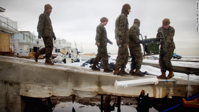 U.S. Marines from the 8th Engineer Support Battallon out of Camp Lejeune, North Carolina, move a generator to pump out floodwater from a street after a nor'easter on Thursday, November 8, in the Breezy Point neighborhood of Queens, New York. The nor'easter, which dumped 2 feet of snow in some places, complicates Superstorm Sandy recovery efforts. That storm killed at least 111 people in the region and knocked out power to millions of customers. See photos of the aftermath of Sandy.