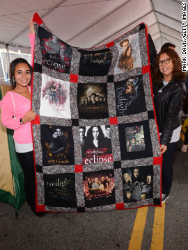 "Two fans hold up a ""Twilight"" quilt."