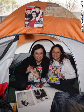 "Fans hold up magazines featuring ""Twilight"" actors Robert Pattinson and Kristen Stewart."