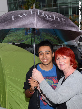 Two fans brave the rain with a &quot;Twilight&quot; umbrella at tent city.