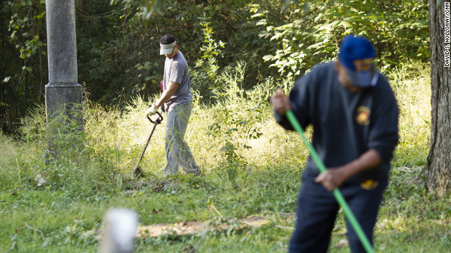 Volunteers clear the overgrown brush from Linwood Cemetery, which tells the story of Macon's African-American community. Sgt. Rodney Davis' mother insisted on burying him there, instead of Arlington National Cemetery. Davis' sister, Debra Ray said: &quot;Mother would say if Rodney wasn't there nobody would care about the cemetery.&quot; 