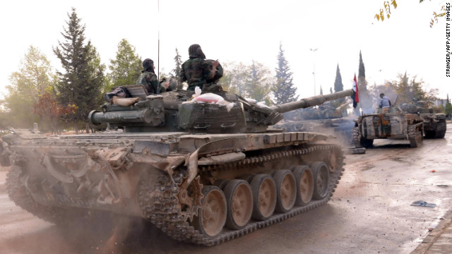 Syrian army soldiers ride along a street Saturday in the northern province of Aleppo.