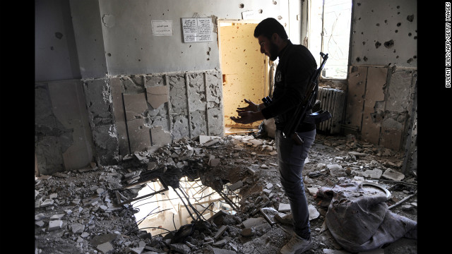 A Syrian opposition fighter stands in a destroyed house in Ras al Ain on Saturday.
