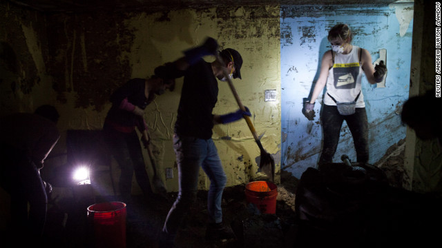 Volunteers shovel sand and water out of the basement of Monir Islam's home in the Rockaway Park neighborhood of Queens, New York, on Sunday. The Rockaways peninsula in Queens was one of the areas hardest hit by Sandy. <a href='http://www.cnn.com/2012/11/09/us/gallery/sandy-rockaway/index.html' target='_blank'>See photos of Rockaway's continuing struggles</a>.