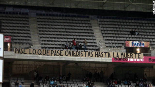 Oviedo fans display a banner in the Estadio Carlos Tartiere reading: &quot;Happen what may, Oviedistas until death.&quot; Of Slim's intervention, an Oviedo statement said: &quot;This challenge and ambition is strictly a sports investment and one that looks to benefit the club and its fans. The investment will try to support Oviedo's players so they can reach their goals and the club can reach the division that corresponds to its history and values.''