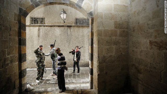 Syrian opposition fighters pass an old man as they patrol the northern city of Aleppo on November 11.