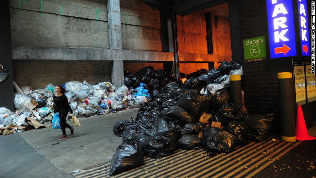 A woman makes her way past trash piles in Lower Manhattan on Monday.