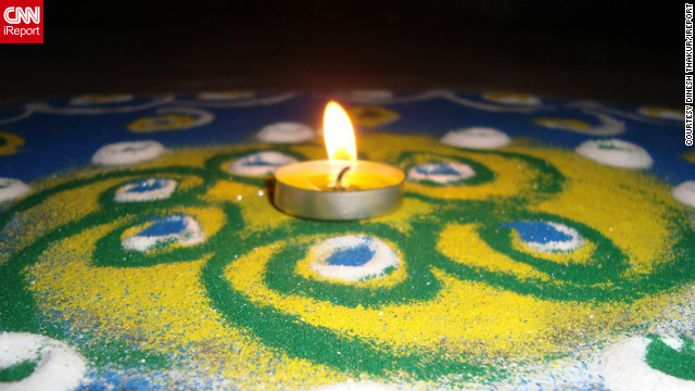 "Diwali is a festival that provides the opportunity to celebrate life with colors as well as lights, says <a href='http://ireport.cnn.com/people/deadspirit6'>Dinesh Thakur</a> of Pune, India. ""It symbolizes victory of good over evil - light defeating darkness. It teaches us to have faith in the 'good' and not give into the darkness,"" he adds. He took this image of a single candle resting above a rangoli artwork to mark the start of this year's festival."