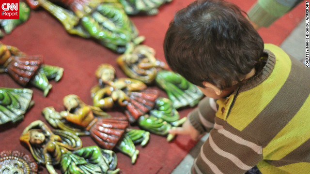 "Manish Kanojia took this image of his daughter, Kyra, reaching out to touch ceramic artifacts on sale at a market in New Delhi, India. The ornamental items are a popular buy around Diwali time when ""people use them to decorate their homes,"" he says."