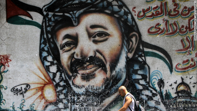 (File photo) A man walks past graffiti depicting late Palestinian leader Yasser Arafat in Gaza on July 17, 2010.
