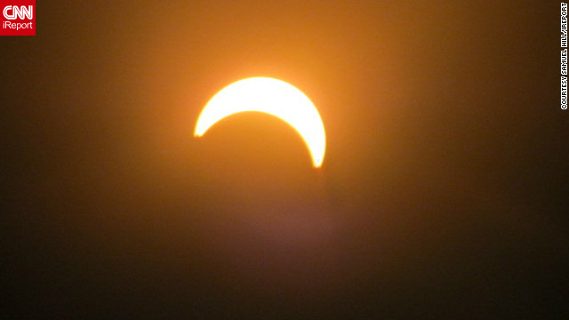 """I thought it would be cool to take a few photos because I haven't seen an eclipse in my lifetime, says iReporter <a href='http://ireport.cnn.com/people/sjhill87'>Samuel Hill</a> who shot this picture in Wellington, New Zealand. ""Most people were really excited once they got to look through the solar lenses to see the eclipse."""