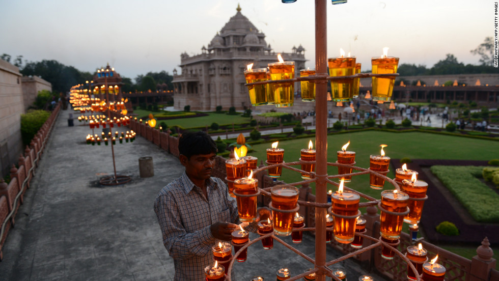 An Indian worker lights lamps at the Akshardham Temple in Gandhinagar during Diwali on Tuesday, November 13. The temple will be lit with thousands of oil lamps until November 18. The festival marks the victory of good over evil and symbolizes taking people from darkness to light.