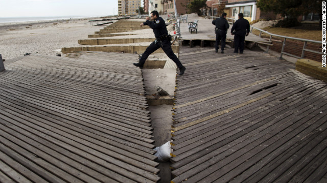 A New York police officer jumps over a large crack in a boardwalk in Brooklyn on Wednesday, November 14. The boardwalk was damaged by the storm surge from Hurricane Sandy. See photos of the immediate aftermath of Sandy.
