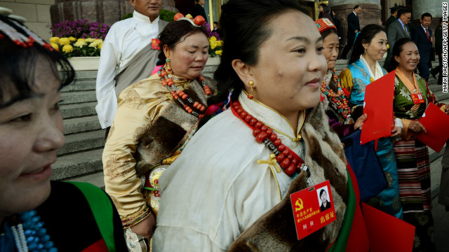 Tibetan delegates carry party documents as they leave the closing ceremony of the Party Congress at the Great Hall of the People in Beijing on November 14.