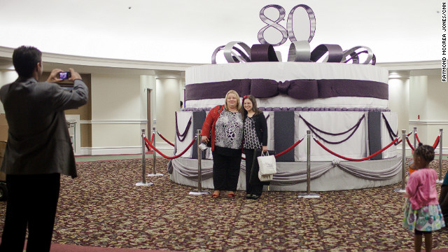 Visitors to First Baptist Church Atlanta stand in front of a birthday cake model honoring Charles Stanley, the church's senior pastor. Stanley, whose televised broadcasts from First Baptist are beamed across the globe, was one of the first pastors to recognize the power of radio and television.