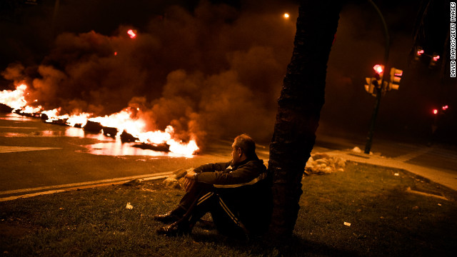 A demonstrator sits next to a barricade of burning tires on November 13, 2012 in Barcelona, Spain.